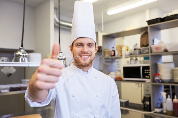 happy chef at restaurant kitchen showing thumbs up Stock photo © dolgachov