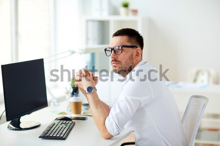 businessman in glasses sitting at office computer Stock photo © dolgachov