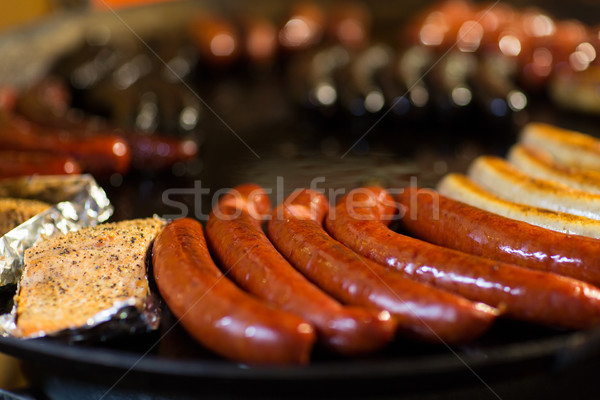 sausages and salmon frying in stir fry pan Stock photo © dolgachov