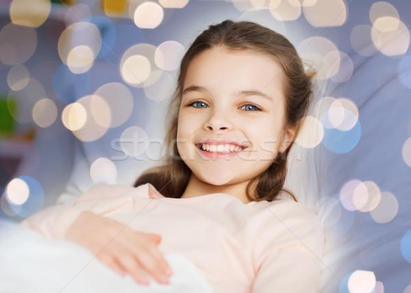 happy smiling girl lying awake in bed over lights Stock photo © dolgachov
