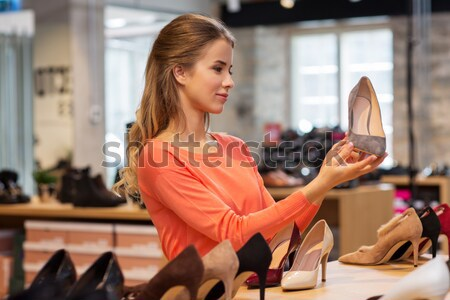 Stock photo: young woman calling on smartphone at shoe store