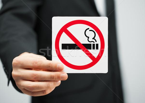 man in suit holding no smoking sign Stock photo © dolgachov