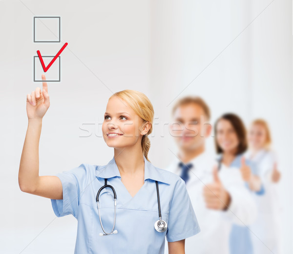 doctor or nurse drawning checkmark into checkbox Stock photo © dolgachov