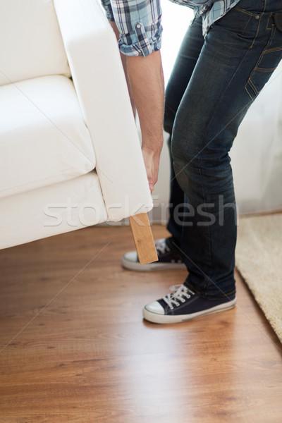 close up of male lifting up sofa to move Stock photo © dolgachov