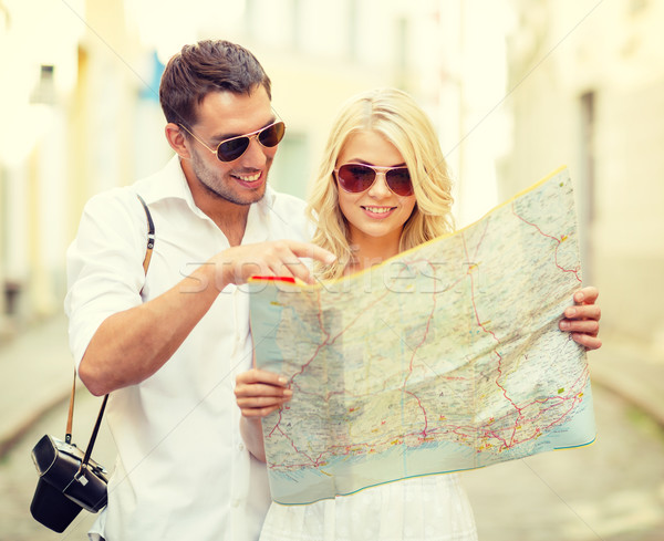 smiling couple in sunglasses with map in the city Stock photo © dolgachov