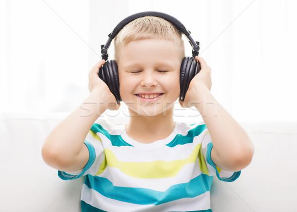 Uśmiechnięty mały chłopca słuchawki domu wypoczynku Zdjęcia stock © dolgachov