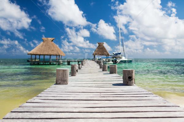 wooden pier with blue water around Stock photo © dolgachov