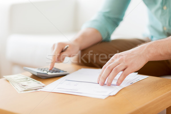 Stock photo: close up of man counting money and making notes