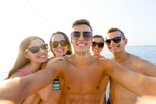 group of smiling friends making selfie on beach Stock photo © dolgachov