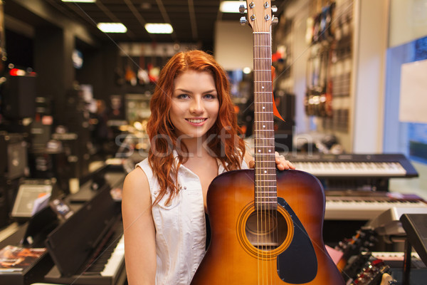Stock photo: assistant or customer with guitar at music store