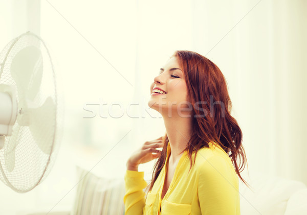 smiling redhead teenage girl with big fan at home Stock photo © dolgachov