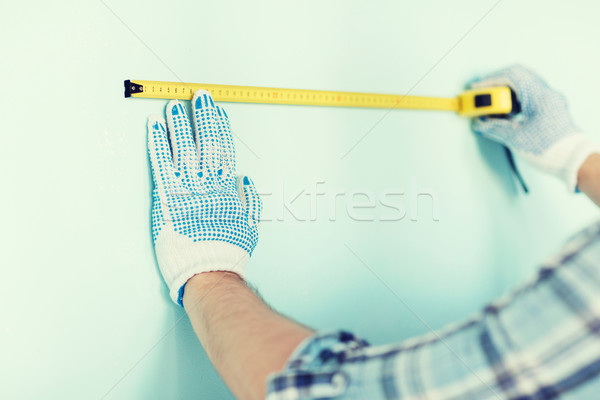 closeup of male in gloves measuring wall with tape Stock photo © dolgachov