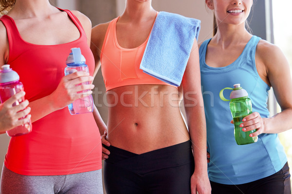 group of women with water bottles in gym Stock photo © dolgachov