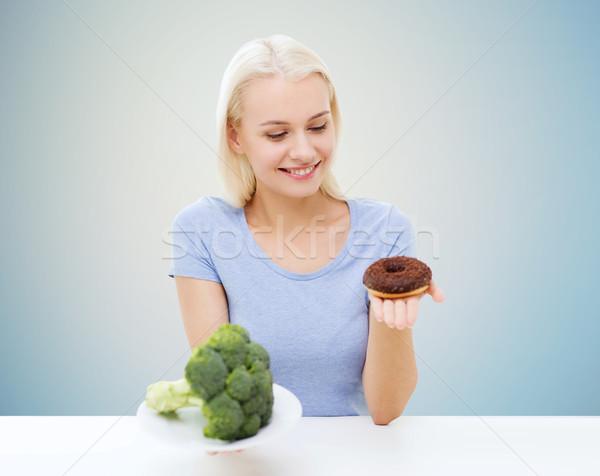 Mosolygó nő választ brokkoli fánk egészséges étkezés egészségtelen étel Stock fotó © dolgachov