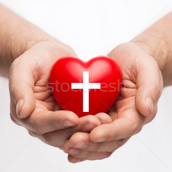 male hands holding heart with cross symbol Stock photo © dolgachov