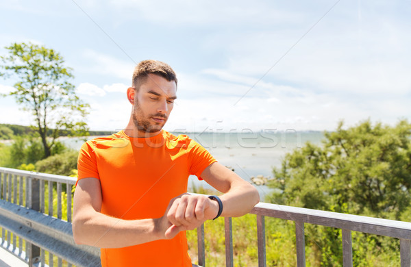 young man with smart wristwatch at seaside Stock photo © dolgachov