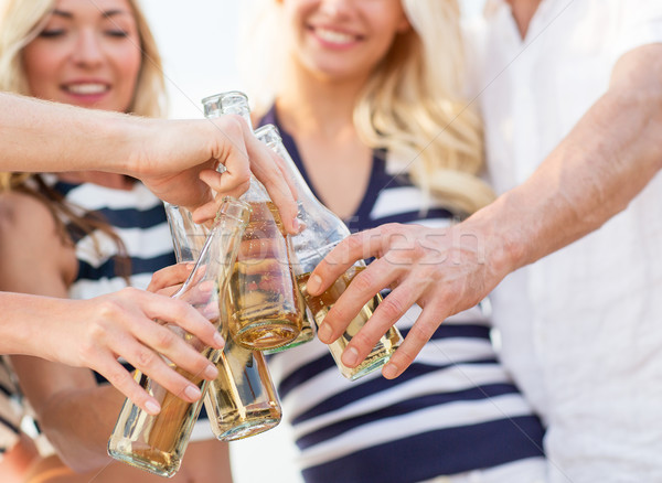 close up of friends clinking bottles with drinks Stock photo © dolgachov