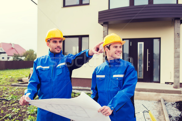 smiling builders with blueprint pointing finger Stock photo © dolgachov