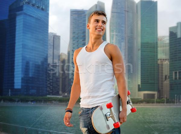 smiling man with skateboard over singapore city Stock photo © dolgachov