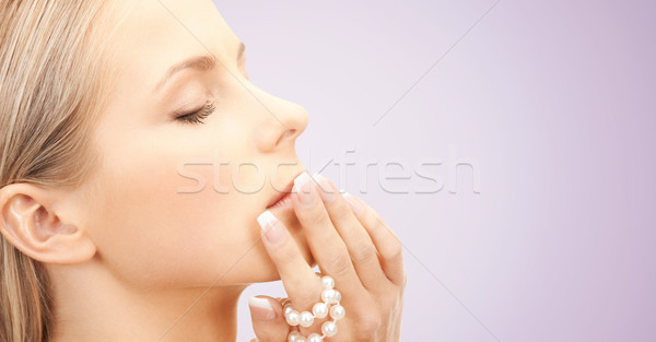 beautiful woman with sea pearls beads over violet Stock photo © dolgachov