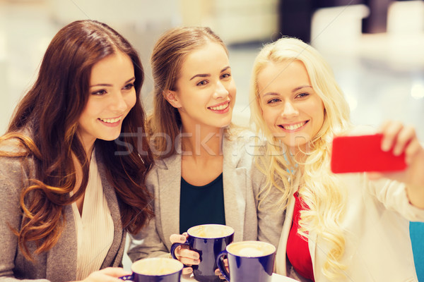 Stock photo: smiling young women with cups and smartphone