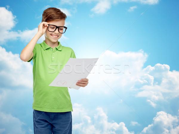 happy boy in eyeglasses holding school test result Stock photo © dolgachov