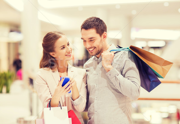 couple with smartphone and shopping bags in mall Stock photo © dolgachov