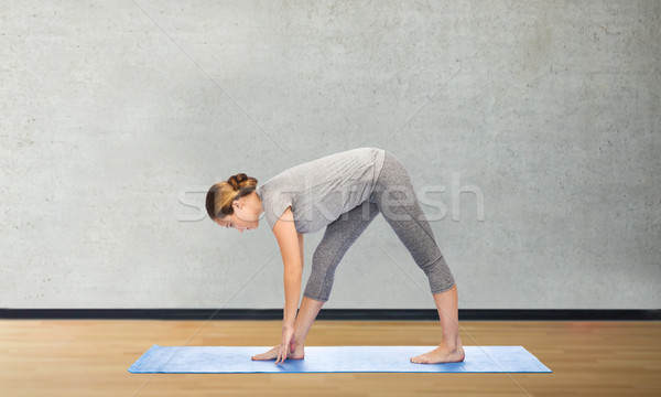 woman making yoga intense stretch pose on mat Stock photo © dolgachov