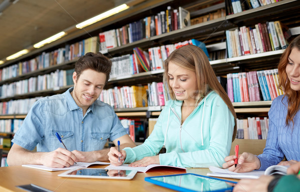happy students with tablet pc in library Stock photo © dolgachov