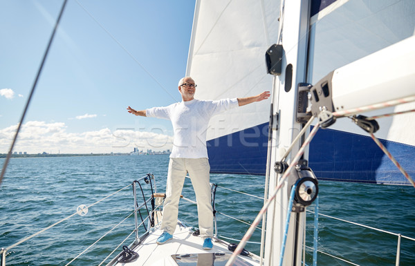 senior man on sail boat or yacht sailing in sea Stock photo © dolgachov