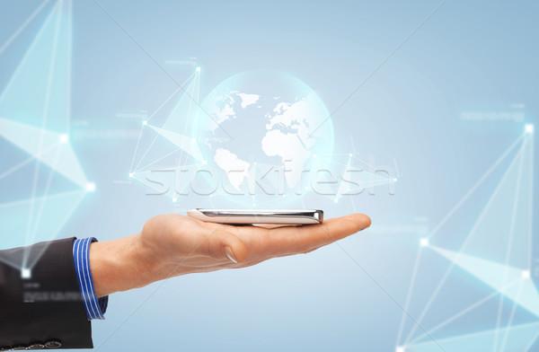 Mannelijke hand smartphone wereldbol projectie mensen Stockfoto © dolgachov