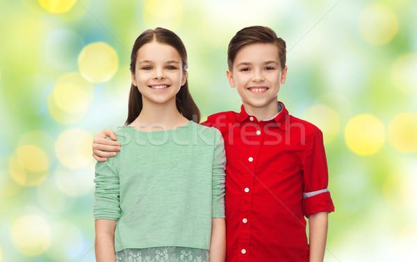 happy boy and girl hugging over green lights Stock photo © dolgachov
