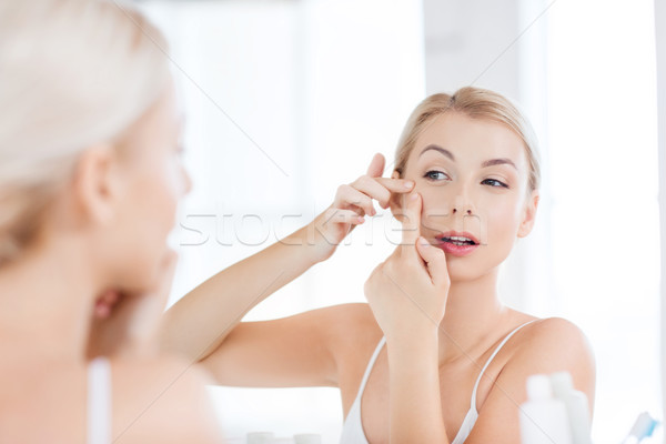 woman squeezing pimple at bathroom mirror Stock photo © dolgachov
