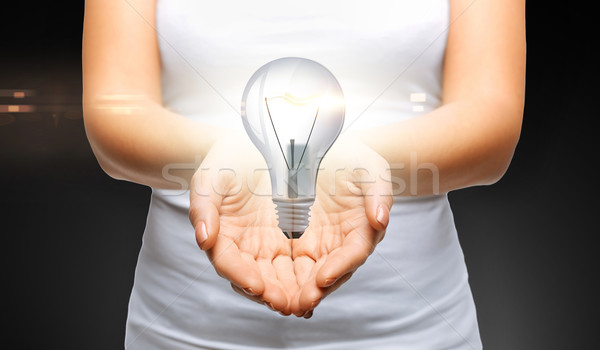 close up of womans cupped hands with light bulb Stock photo © dolgachov