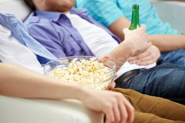 close up of friends with beer and popcorn at home Stock photo © dolgachov