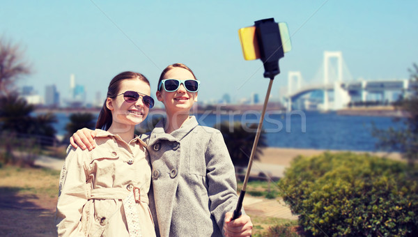 happy girls with smartphone selfie stick in tokyo Stock photo © dolgachov