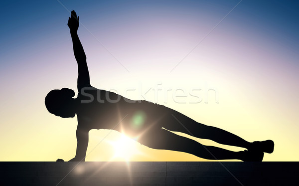 woman doing plank exercise on stairs over sunlight Stock photo © dolgachov