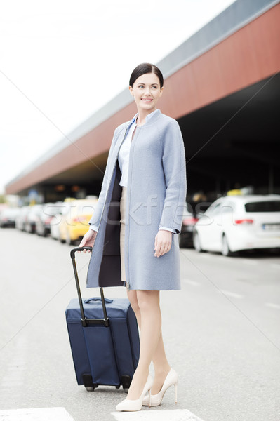 smiling young woman with travel bag over taxi Stock photo © dolgachov