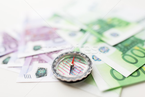 close up of compass and euro money on table Stock photo © dolgachov