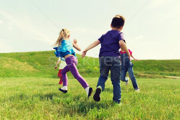 group of happy kids running outdoors Stock photo © dolgachov