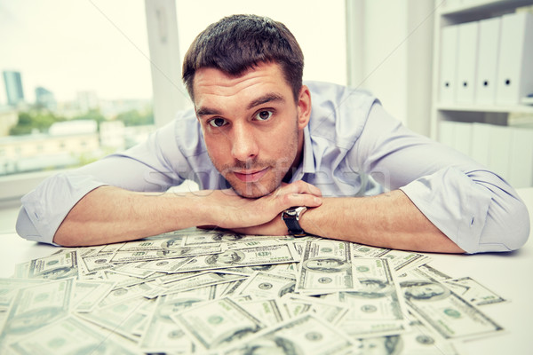 happy businessman with heap of money in office Stock photo © dolgachov