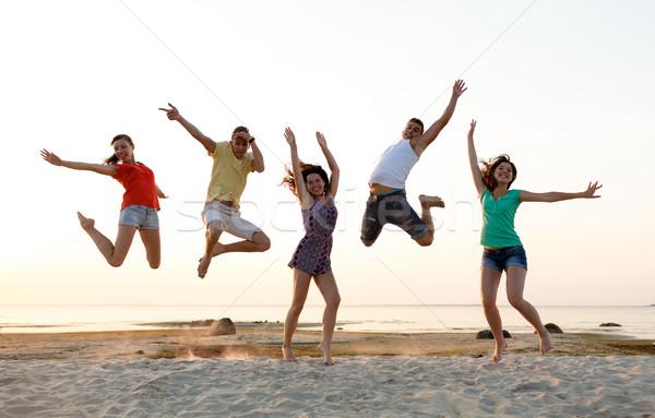 Mosolyog barátok tánc ugrik tengerpart barátság Stock fotó © dolgachov