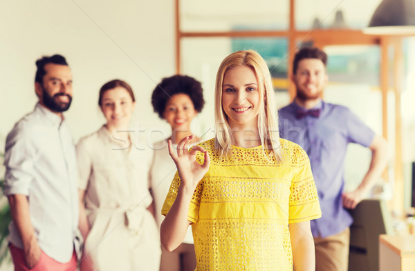 happy woman showing ok over creative office team Stock photo © dolgachov