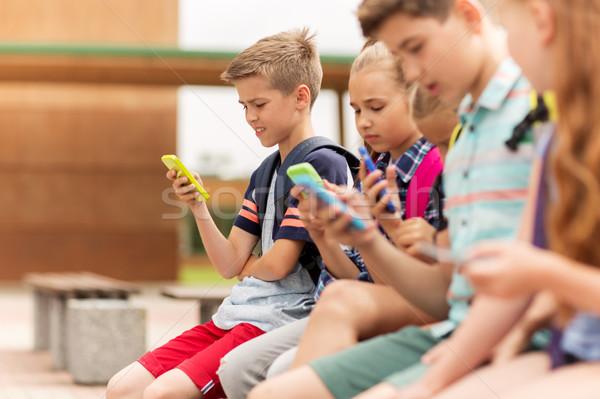Foto stock: Escuela · primaria · estudiantes · smartphones · primario · educación · amistad