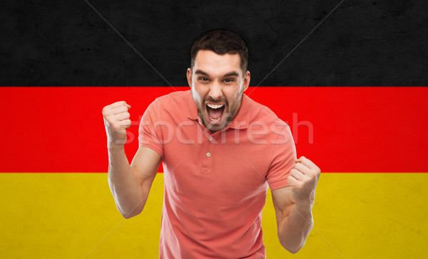 angry man showing fists over german flag Stock photo © dolgachov