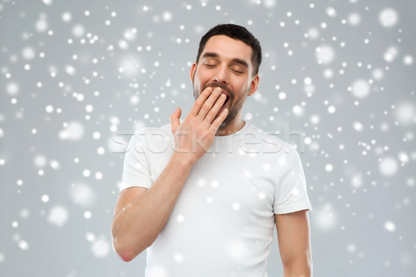 tired yawning man over snow Stock photo © dolgachov