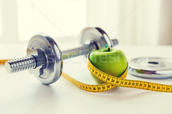 close up of dumbbell and apple with measuring tape Stock photo © dolgachov