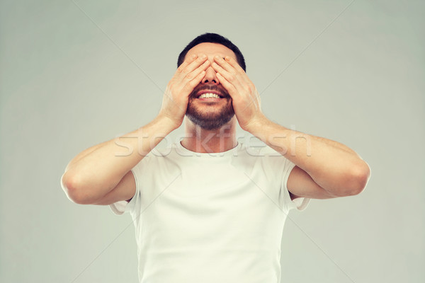 smiling man closing his eyes over gray background Stock photo © dolgachov