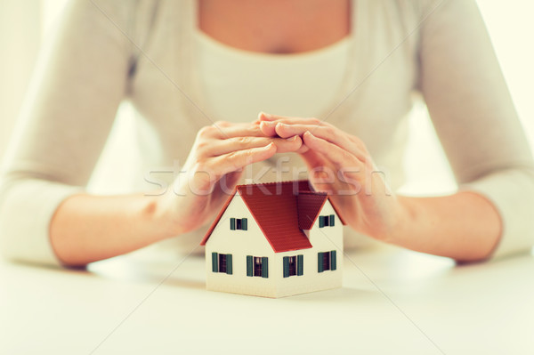 close up of hands protecting house or home model Stock photo © dolgachov