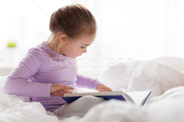 happy little girl reading book in bed at home Stock photo © dolgachov